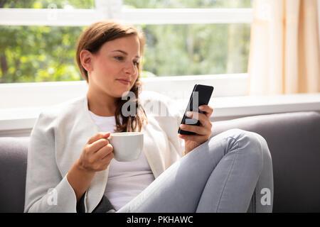 Junge Frau mit Tasse Kaffee mit Handy - Stockfoto
