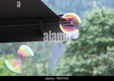 Eine schöne Zwei Blasen in verschiedenen Farben erstellt bubble Blume. Im Hintergrund gibt es das Dach und den Wald. Eine ist Grün und Lila, Lila - Stockfoto