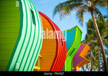 Abstrakte Reihe von bunt bemalten bunte Rettungstürme mit Kokospalmen am Miami Beach Promenade. - Stockfoto
