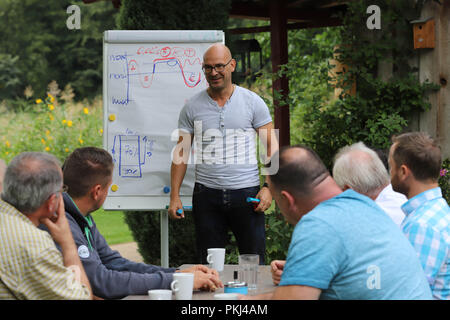 """Behavioral Trainer während einer Vorlesung zum Thema """"Stressmanagement"""" in einen sommerlichen Garten in Brandenburg/Deutschland. - Stockfoto"""