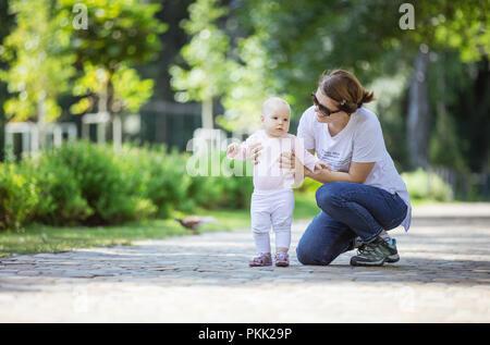 Mutter, Tochter und helfen, ihre ersten Schritte machen. Mutter und Tochter auf Spaziergang im Sommer Park. - Stockfoto