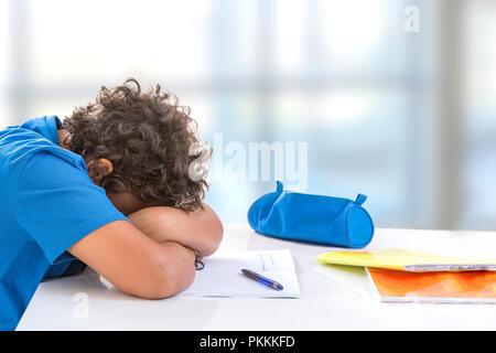 Überwältigt Schüler. Gelangweilt und müde Teenager Hausaufgaben am Schreibtisch in seinem Zimmer, scheint sleepinp - Stockfoto
