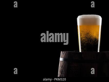 Kalten Glas Handwerk Bier auf alten Holzfass auf schwarzem Hintergrund mit Tau und Blasen. Mit Platz für Ihren Text. - Stockfoto