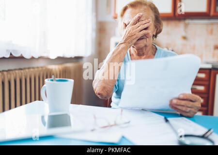 Ältere Frau auf ihre Stromrechnungen und Schreibarbeit suchen - Stockfoto