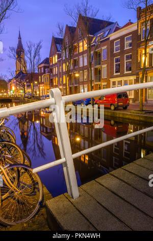 Am Abend Blick auf den Kanal und die Kirche in Delft. Niederländische Stadt im Frühjahr nach Sonnenuntergang. Holland, Niederlande. - Stockfoto