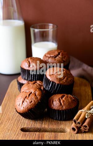 Hausgemachte Schokolade Muffins (Brownies) mit Zimt und Milch auf braunem Papier Hintergrund Stockfoto