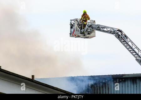 Feuerwehrmann Kämpfen Feuer In Einer Fabrik In England Stockfoto