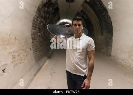 Jungen 20-25 Jahre alten Mann, der in der Tunnelbauweise mit Skateboard. Umgebungslicht Bild (Bild haben einige Geräusche) - Stockfoto