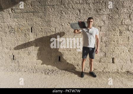 Junger Mann, der in der Tunnelbauweise mit Skateboard posing - Stockfoto