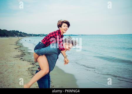 Junge Männer, die piggyback Ride zu den Frauen am Strand. Junges Paar Spaß zusammen mit Blue Ocean Hintergrund. Konzept der Liebenden glücklichen Momente auf Fei - Stockfoto
