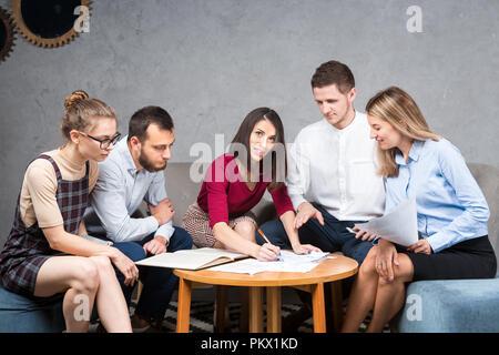 Thema Geschäftslage, Teamarbeit. Gruppe von jungen kaukasischen fünf Menschen im Büro an einem runden Tisch sitzen, mit Papier, Grafik. - Stockfoto