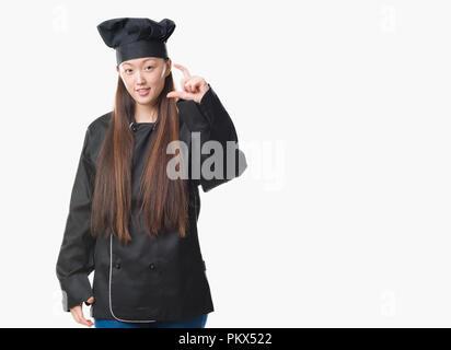 Junge chinesische Frau über isolierte Hintergrund tragen Küchenchef einheitliche lächelnd und selbstbewusst und deutete mit der Hand tun Größe Schild mit Fingern auf der Suche - Stockfoto