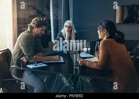Business Team in einem Raum zu sitzen und zu diskutieren. Profis sitzen um einen Tisch Brainstorming Ideen. - Stockfoto