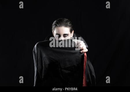 Frau in einem Vampir Kostüm für Halloween. Studio Aufnahme einer jungen Frau in Dracula Kostüm auf schwarzem Hintergrund - Stockfoto