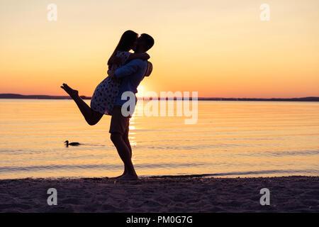 Silhouette von glückliches Paar am Strand bei Sonnenuntergang, Mann nimmt das Mädchen in seine Arme. - Stockfoto