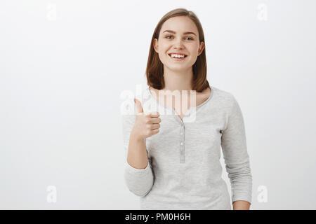 Ich gebe Idee Daumen nach oben. Gerne glücklich charmante junge europäische Frau mit kurzen braunen Haaren lächelnd mit fröhlichen Ausdruck mögen gut Aussehen von Freund beim Versuch, auf Neue outfir zur Genehmigung über graue Wand - Stockfoto