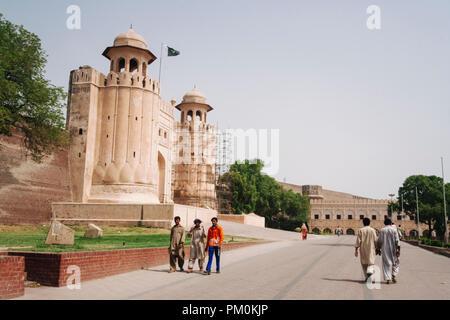 Lahore, Punjab, Pakistan, Südasien: Menschen gehen vorbei an der riesigen Alamgiri Tor der Shahi Qila oder Lahore Fort, im Jahre 1674 während der Regierungszeit von gebaut - Stockfoto