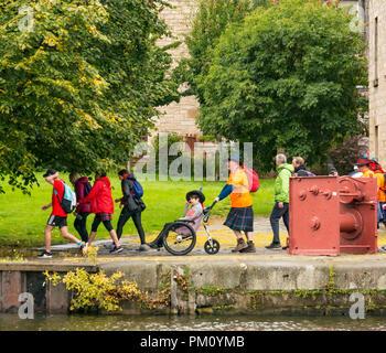 Leith, Edinburgh, Schottland, UK, 16. September 2018. Edinburgh Kilt gehen, das letzte der vier Kilt geht in diesem Jahr nach den in Glasgow, Aberdeen und Dundee, durch die königliche Bank von Schottland gesponsert, findet heute statt. Wanderer, Kapital für eine Wohltätigkeitsorganisation Ihrer Wahl. Es gibt drei Fuß Längen: Die volle 24 Meilen vom Holyrood Park zu BT Murrayfield Stadium und zwei kürzere Wanderungen von 15,5 und 5 Meilen. Der Kilt Wanderer erreichen Das Ufer in Leith bei ca. Km 14, ein Mann mit einem Kilt drücken Eine behinderte Frau in einem Rollstuhl am Flussufer - Stockfoto