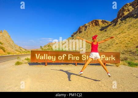 Junge Mädchen an Touristen willkommen Zeichen Eingang der Valley of Fire State Park springen. Sommer Reisen Urlaub in Nevada, United States. Tal des Feuers ist in der Mojave Wüste 58 Meilen von Las Vegas entfernt. - Stockfoto