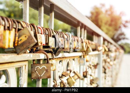 Viele alte rostiges Metall Schlösser geschlossen am Zaun der Brücke über den Fluss. Liebe für immer durch die Zeit. - Stockfoto