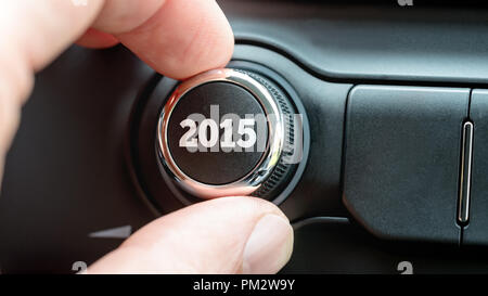 Mann einen Drehknopf oder elektronischer Regler mit dem Datum 2015 auf der Oberseite, wie er den Beginn des neuen Jahres in einem konzeptionellen Bild feiert. - Stockfoto