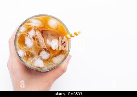 Ice latte oben Blick aus der Nähe auf weißem Hintergrund und Beschneidungspfade. Mit kopieren. Die Hand einer Frau hält ein Glas kalten Kaffee. - Stockfoto