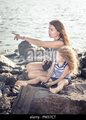 Kleines Mädchen und Mutter weit weg auf der Suche mit dem Fernglas, sitzt auf einem Felsen in der Nähe eines Meeres - Stockfoto