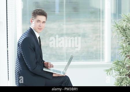 Junge Mitarbeiter, die an einem Notebook arbeitet im Korridor von Th sitzen - Stockfoto