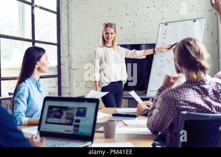 Arbeiten hart, um zu gewinnen. Geschäftsfrau, die Durchführung einer Präsentation mit Flipchart, während in der kreativen Arbeiten im Büro. - Stockfoto