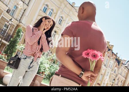 Romantische Überraschung. Junge diverse Paar stand auf der Straße der Stadt Freund holding Blumenstrauß hinter Rücken, während Freundin auf ihn schaut lächelnd heiter - Stockfoto