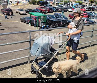 А Vater trägt vorsichtig Baby und Fahrten entlang der Uferstraße, von einem Hund begleitet - Stockfoto