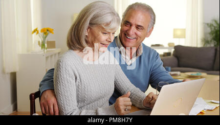 Glückliches junges Paar mit Laptop Computer, Rechnungen zu bezahlen - Stockfoto