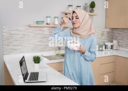 Schöne junge Frau trägt Hijab essen eine Schüssel Müsli wit - Stockfoto