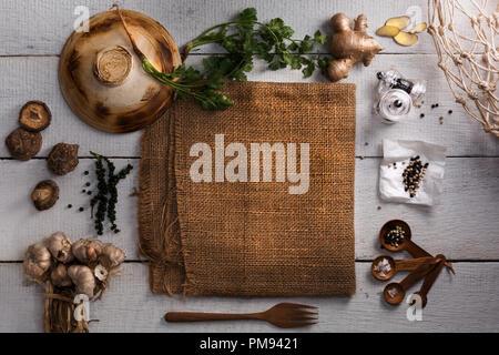 Thai Food Zutaten zum Kochen mit Ingwer, Koriander, Pfeffer, Salz, Knoblauch, lackiert, Gabel, Topf Deckel und Sack auf weißem Holzbrett Hintergrund. - Stockfoto