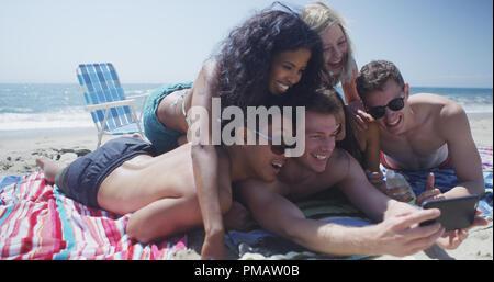 Junge Erwachsene Gruppe von interracial Freunde Lügen unter selfie am Strand - Stockfoto