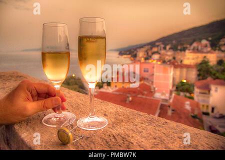 Zwei gefüllte Champagnergläser mit eines Menschen Hand ein Glas auf einem Balkon mit Blick auf das Dorf und die Adria in Kroatien Holding - Stockfoto