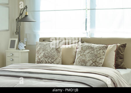 Luxuriöse Schlafzimmer mit Lampe und Wecker auf hölzernen Tisch - Stockfoto