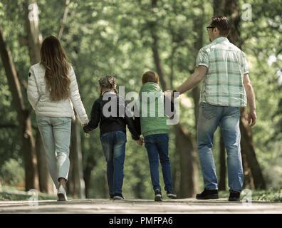 Ansicht der Rückseite. Familie mit zwei Kindern gehen Hand in Hand im Park. - Stockfoto