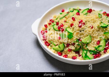 Couscous Salat mit Granatapfel, Minze und Gurken, gesunde Hausmannskost, vegane Mahlzeit - Stockfoto