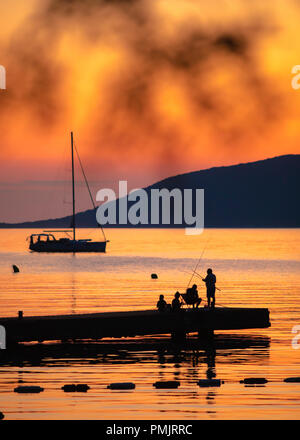 Silhouette von Menschen Angeln auf dem Meer bei Sonnenuntergang. Schöne Meer Sonnenuntergang Szene. - Stockfoto