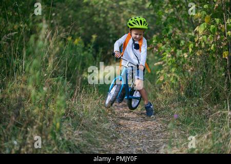 Ein kleiner Junge auf einer Balance bike führt einen Sprung auf einem Pfad in den Wald auf einen Sommer sonnigen Tag - Stockfoto