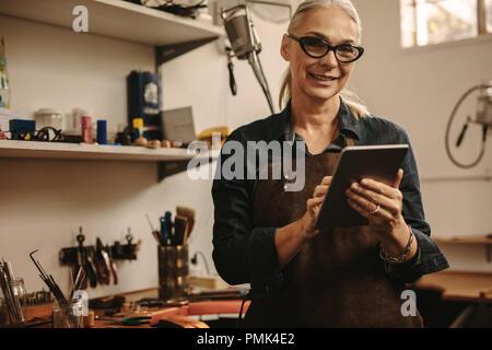 Portrait von Happy reife Frau Schmuck Teekocher mit digitalen Tablet in Ihrer Werkstatt. Lächelnde ältere Frau in goldschmied Workshop mit Tablet-PC. - Stockfoto