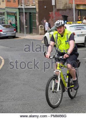 Gardaí- Offizier auf Fahrrad Patrouille mit Helm und reflektierenden Weste, Fishamble Street, Christchurch, Dublin, Leinster, Irland - Stockfoto