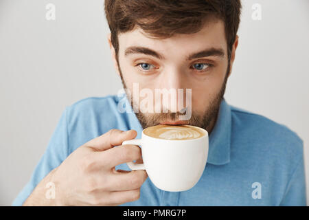 Nahaufnahme der netten Hipster bärtigen Kerl schlürfen Cappuccino im Cafe arbeiten als Freelancer, schöne Atmosphäre und konzentriert wird, über grauen Hintergrund. Frau machte ihn zum Kaffee am Morgen - Stockfoto