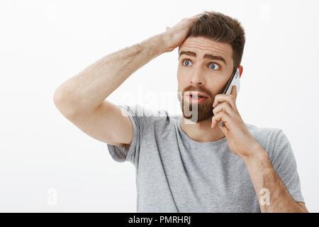 Besorgt und beunruhigt besorgten Freund empfangen von schlechten Nachrichten bei Anruf Haltearm auf Stirn, besorgt und ratlos stehen verwirrt und ratlos über graue Wand - Stockfoto