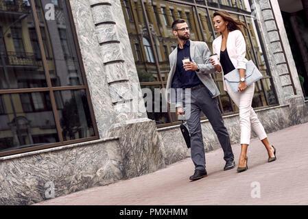 Hast für Treffen. Zwei junge Business Leute draußen auf der Straße trinken heißen Kaffee sprechen lächelt Fröhlich - Stockfoto