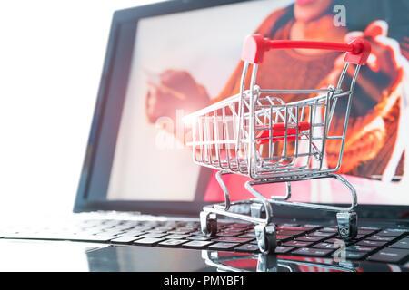 Online shopping Konzept. Warenkorb Trolley auf dem Laptop mit Girl holding Kreditkarte Hintergründe - Stockfoto