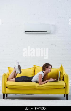 Glückliche junge Frau mit Laptop auf der Couch unter Klimaanlage hängen an der Wand liegen - Stockfoto