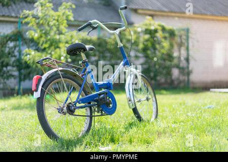 Kinder Fahrrad auf dem Gras. Blau jugendlich Fahrrad auf einem grünen Rasen im Hof. - Stockfoto