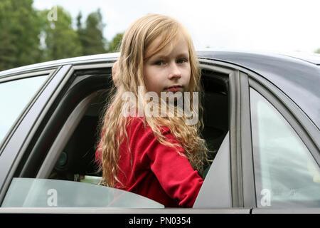 Kleines Mädchen mit langen blonden Haaren und in einer roten Jacke sieht durch das offene Fenster des Autos in die Kamera, kletterte aus dem Fenster, um die Taille, - Stockfoto